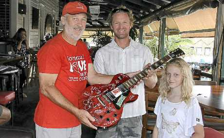 TREASURE: Dave Godfrey picks up his signed Gibson Les Paul Studio guitar with daughter Misty from Cystic Fibrosis charity co-ordinator Alan Tunks at The Balcony.