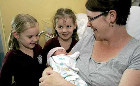 Tanika and Shari Tribe meet their new baby sister, Kaycee Michelle, yesterday after mum Megan Tribe gave birth in the car on the way to hospital.