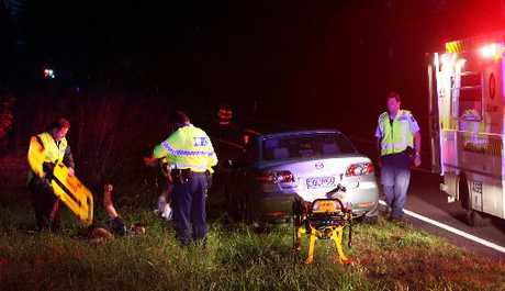 The driver (on the ground with his arm in the air) of a white Suzuki which left the road south of the Chook and Filly restaurant in Maraekakaho escaped a head-on collision but didn't come away scot-free. Photo / Glenn Taylor
