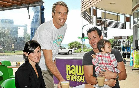 Coolum Raw Energy owner Jimmy Carruthers serves lattes to locals Xian Findlay and Dan Haywood.
