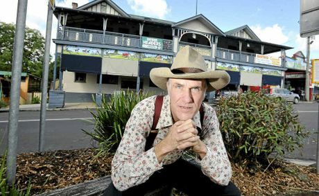 Lismore artist Jimmy Willing in front of his new murals under the veranda of the Nimbin Hotel.