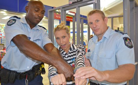 Tamara Ravs gets locked up by constable Jackson Oberia and Senior Constable David Wilkinson as part of a fundraiser for Inala PCYC.