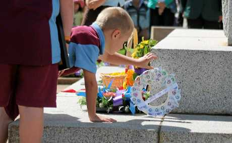 Zach Colless lays his hand-made paper wreath at the cenotaph.