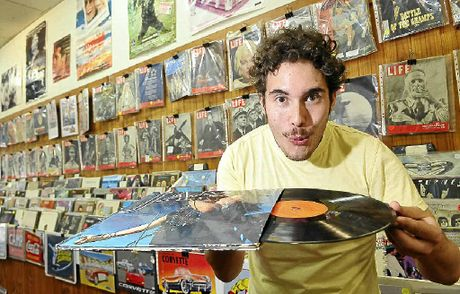 Daniel Stuth blows some dust off a record in the Time Machine after buying the shop with Benjamin Paskins and Barton Worthington.