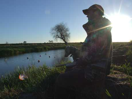 A duck hunter and his dog wait patiently at a private pond