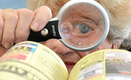 SMALL PRINT: Nina Higgins says she has to use a magnifying glass to read the small print in the new phone book.