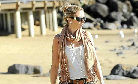 Kirstie Oldham strolls along the beach at Bargara yesterday despite some chilly temperatures.