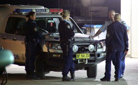 Police officers discuss the armed hold up at the Caltex Service Station in Toormina.