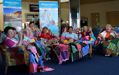 Boambee Gardens residents and a selection of the wonderful blankets they've knitted.