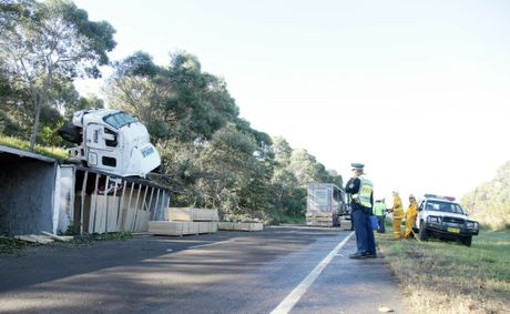 Police, RMS and emergency service workers continue clearing the south-bound lanes of the Pacific Highway following a B-Double roll-over early this morning.