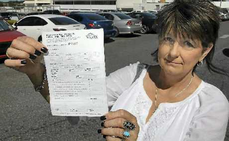 Sher Hennessy holds up her sons parking ticket outside Rockhampton Hospital.