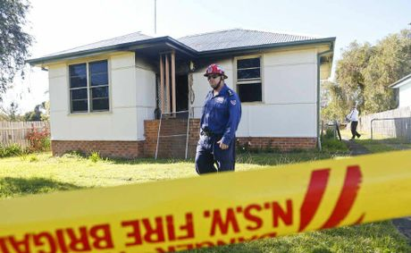 Fire Rescue NSW Grafton Station officer Michael Kearns in front of a property where a woman died in a house fire.