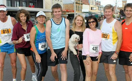 Katie McKean (middle with dog) is in hospital after being hit by a car while jogging in Brisbane. She's pictured with her family (from left) David McKean, Lilian Armitage, Noela and Kurt Ensbey, Taz McKean, Niel Ensbey and her husband Tom McKean after the 2010 Warwick Pentath-run.