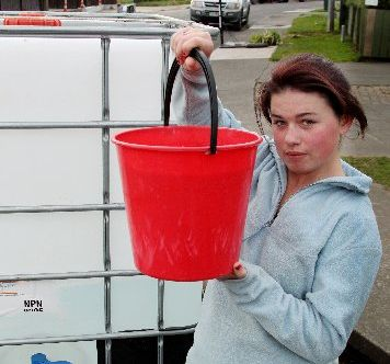 Rian Whitaker, 17, collects some water from a tank set up by the Hastings District Council for people on Manuka St in Hastings to use.