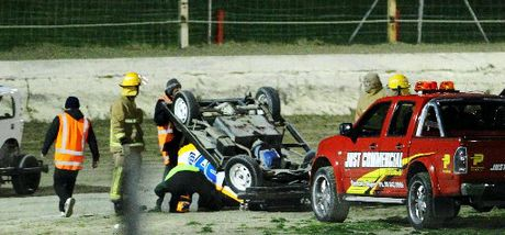 Rescue crew personnel check on the wellbeing of Hawke's Bay ministock driver Brandon Warner after he flipped during the first ministock heat at Meeanee on Saturday night. Photo / Glenn Taylor