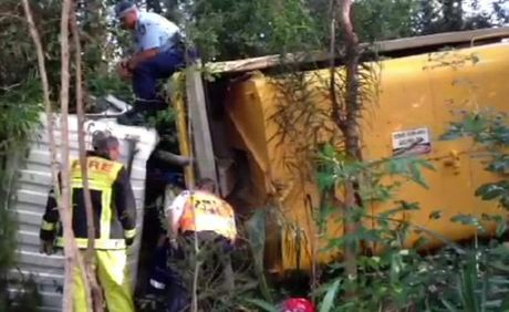 A driver is trapped inside a truck which has rolled on the Pacific Highway north of Coffs Harbour outside Novotel Pacific Bay.