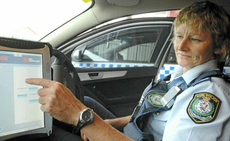 Highway patrol supervisor Sergeant Jodie Hamilton with the mobile automatic number plate recognition system that has made rego stickers obsolete.