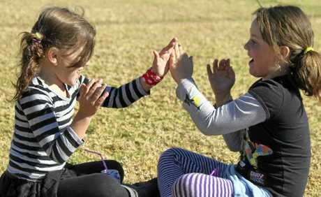 Ella Talbot and Nadine Sampson play clapping games in the sunshine at the weekend.