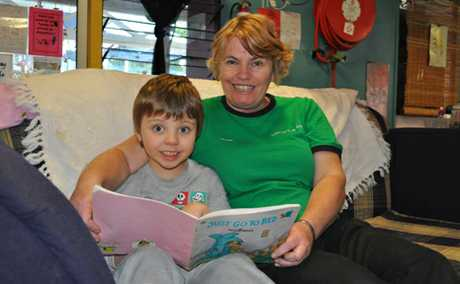 WELL DONE: Rosie's kindergarten teacher Judith Williams, who was named Queensland educator of the year, reads a book to student John Henry Noakes.