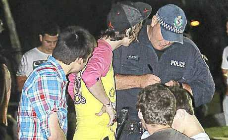Police speaking with youths in a Byron Bay park.