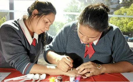 Miranda Fisher (right) paints a hand tattoo on friend Whitley Jacobs.