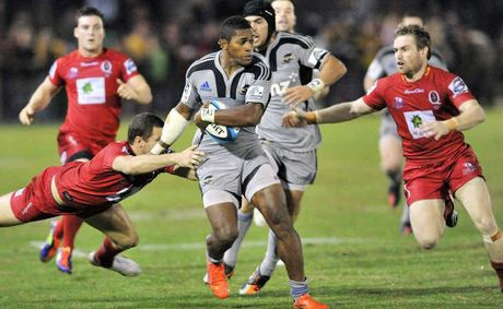 The Wellington Hurricanes' Alapati Leiua keeps a cool head under pressure from the Reds at Bokarina last night.