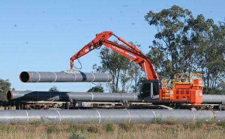UNLOADING: Coal seam gas pipes transported from Gladstone Harbour by train are unloaded at Australian Pacific LNG's Callide stockpile site.
