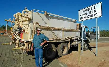 NEW FACILITY: Larry Kiernan stands near his water truck after uncovering the sign at the new breakdown facility.