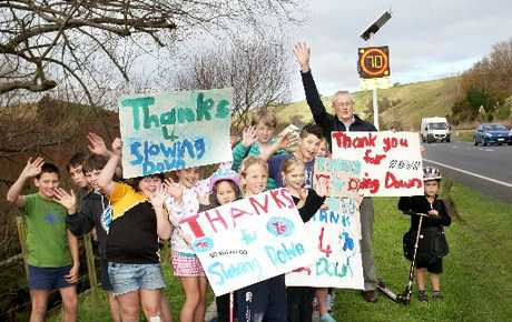 THANKS, CARS: Principal Alastair White and students of Kai Iwi School hold up messages thanking the traffic for slowing down outside their school. PHOTO/BEVAN CONLEY 210612WCBRCSC01