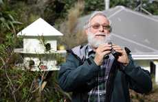 John Staniland stands in his garden bird watching for the New Zealand Garden Bird Survey.