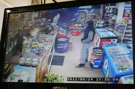 This CCTV image shows an armed man (centre), point a metre-long machete at The Korna Store owner Hetal Mistry who is running away as another robber jumps the store&#39;s counter, during an aggravated robbery on Sunday.