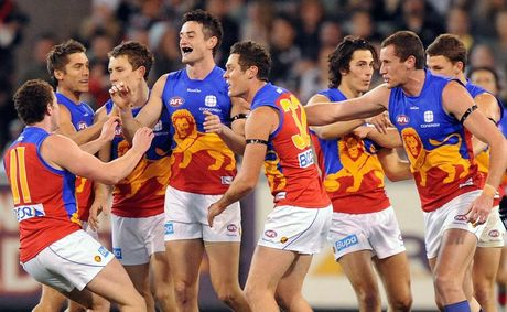 Niall McKeever of the Brisbane Lions is congratulated by team-mates after kicking his first career goal in 2011.
