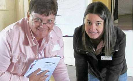 HELPING HAND: CSG project officer Kate Dunn helps landholder Jo Whip, Morven, identify CSG tenures in the region at a CSG information session.