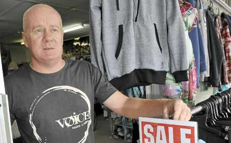 Voice Clothing owner Stuart Bendle at his shop where thieves broke and stole cash and goods, and inset the smashed window used to gain entry.