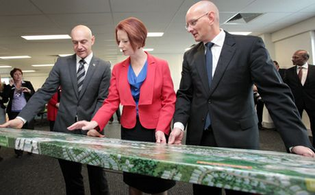Prime minister Julia Gillard looks at development plans for the new Springfield Cancer Care Centre with federal member for Blair Shayne Neumann and federal member for Oxley Bernie Ripoll.