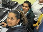 Warwick East students Jessica Lewis, Malikah Woodbridge and indigenous teacher aide Corin Donges working on the 'Ollie-Up' learning program.