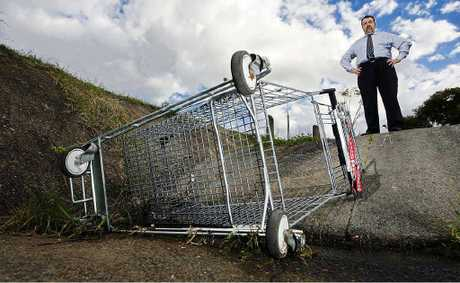 Councillor Paul Tully looks at an abandoned trolley in a gully at Goodna.