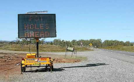 A sign warns of potholes on the Bruce Hwy at Archer.