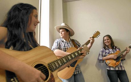 Young country musicians Tia Gostelow (left), Damien Agius and Karrie Hayward give an impromptu performance at the Daily Mercury's office after their interview.