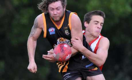 Grafton Tigers' Ronald Davis gets the ball away despite the best efforts of a Coffs Swans defender at Fitzroy Oval on Saturday.