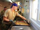 Private Jason Newmann lays out dinner as troops line up in the mess at Patrol Base Sorkh Bid.