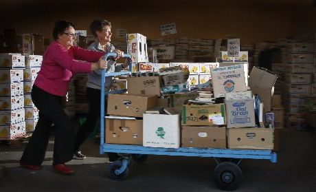 Anne Richards (left) and Wendy Brice wheel a load of second hand books into the sorting bay in preparation for this year's great book sale.