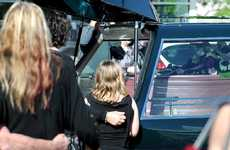 Natasha McCarthy's daughter, Aiesha Whitmore, is comforted as her mother's casket is placed in the hearse.