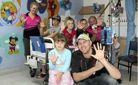 SEA FM's Jay Shipston (front), Liana Ladner and Dave Peters visit (from left on the bed) Dayne Andrews-Grant, Jessica Wetherby, Caleb Henderson and Gabrielle Page (front) at the Mackay Base Hospital children's ward.