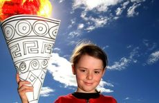 Sidera Dyer, age 8, holds the torch aloft.