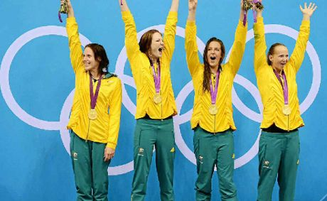 Brittany Elmslie (second from right) and Melanie Schlanger (right) celebrate with Alicia Coutts and Cate Campbell on the podium after winning the women's 4 x 100m freestyle relay final in Olympic record time.
