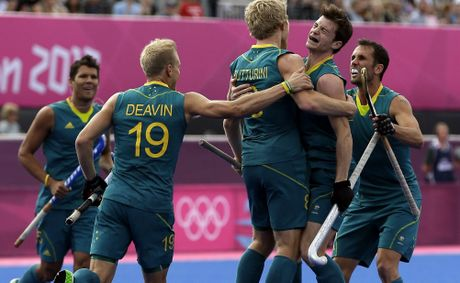 Australia&#39;s Matthew Butturini (8) celebrates his goal with teammates during their men&#39;s hockey preliminary match against Spain at the 2012 London Olympics.