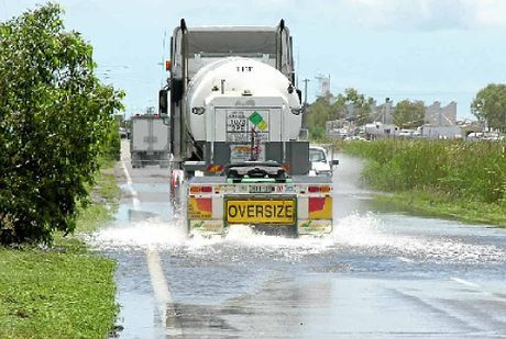 ABOVE AND BELOW: Trucks cross a flooded Blakey's Crossing near Townsville.