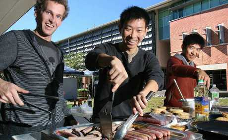 Jeremy Wright, Tze Chin and Ethan Xu cook kangaroo snags and vegie patties at the University of Queensland Ipswich campus's Sustainability Market yesterday.