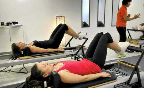 Kristen Ehrlich (front) and Christel Pidcock take part in a reformer pilates led by instructor Sonya Morgan.